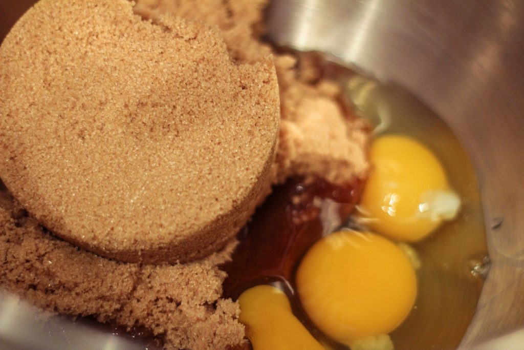 brown sugar and 3 eggs in a mixing bowl