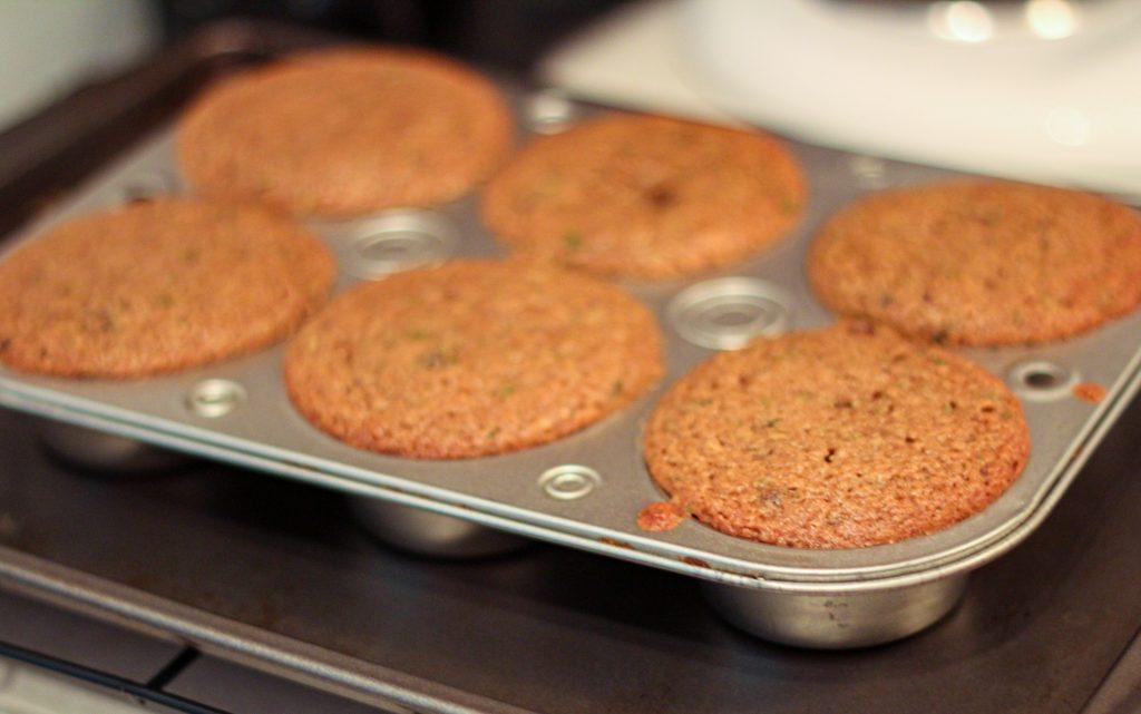 six zucchini muffins in a muffin baking pan