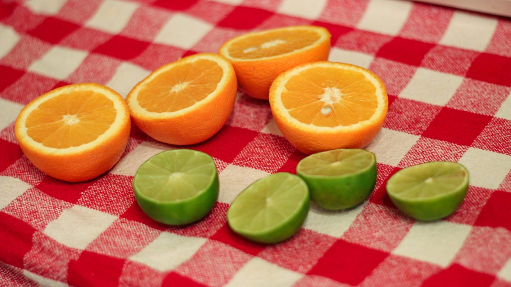two oranges and two limes sliced in half