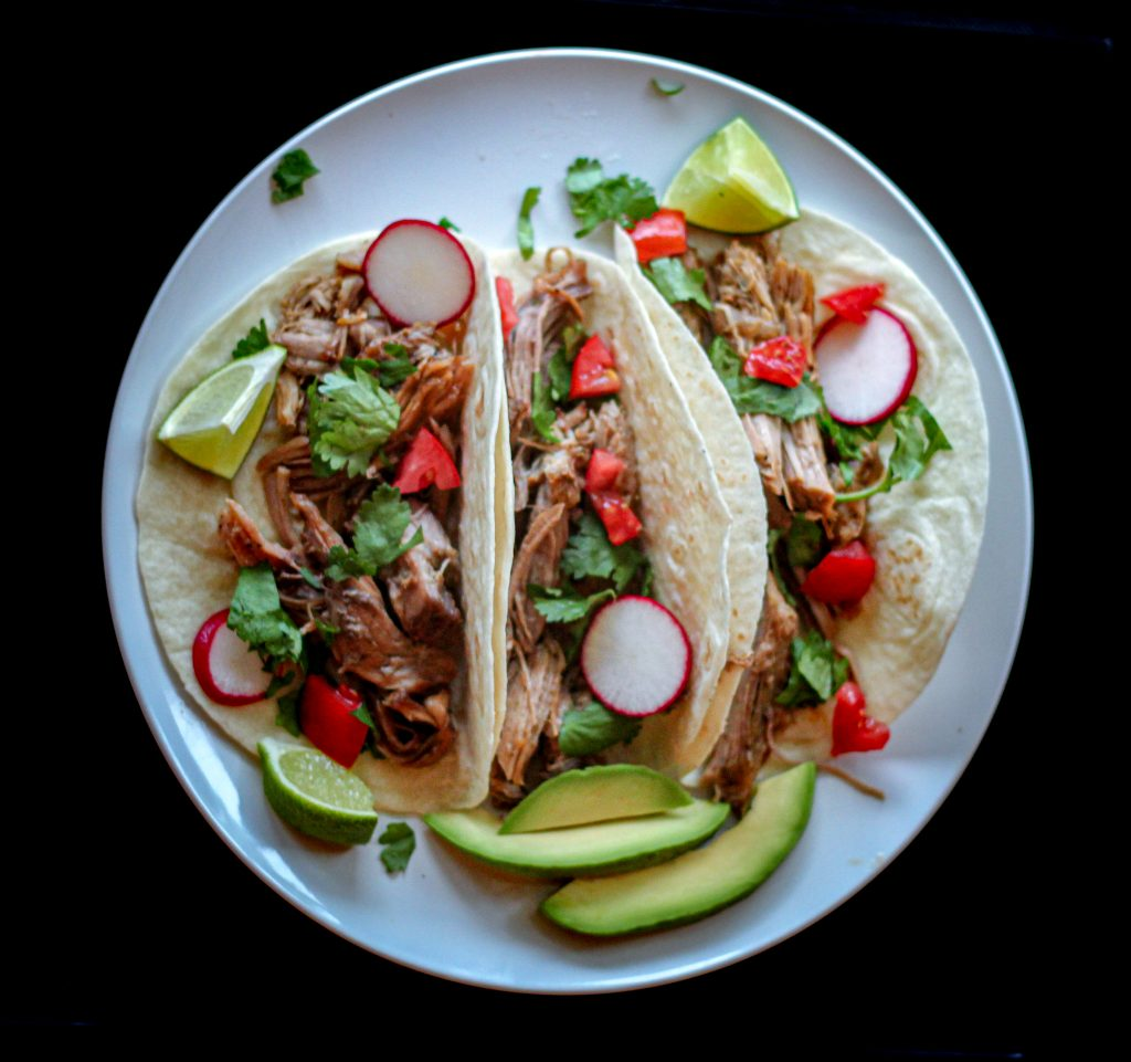 three pork carnitas tacos in flour tortillas with avocado slices on the side