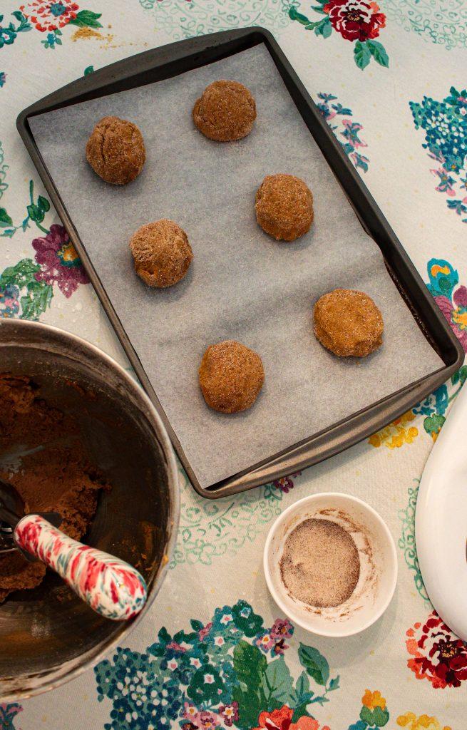6 gingersnap cookie dough balls on a baking sheet