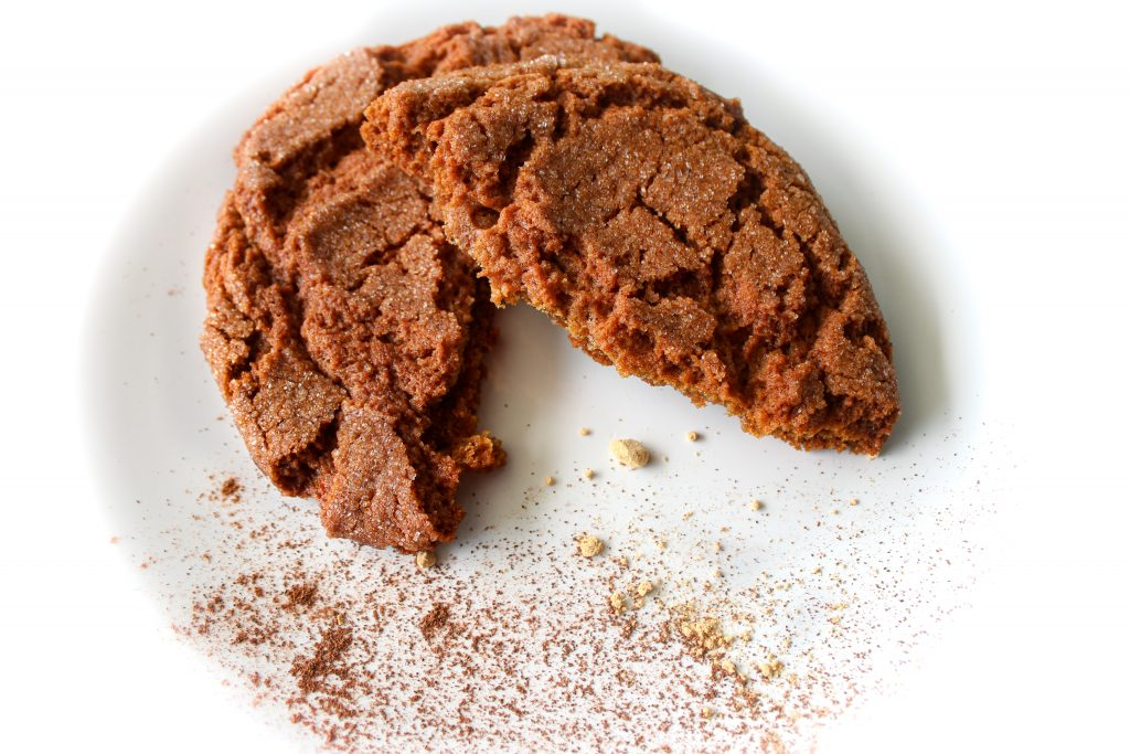 Broken gingersnap cookie on a plate with cinnamon