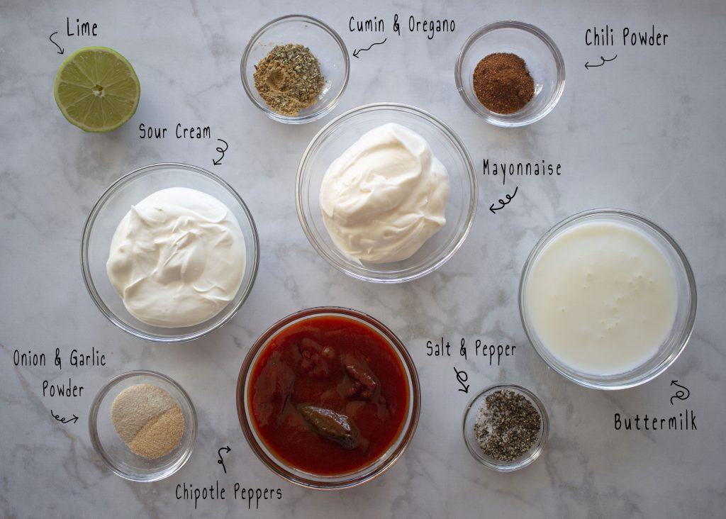 Ingredients used to make the chipotle salad dressing. These include: Lime, Cumin, Oregano, Chili Powder, Sour Cream, Mayonnaise, Onion Powder, Garlic Powder, Chipotle Peppers, Salt, Pepper, and Buttermilk.