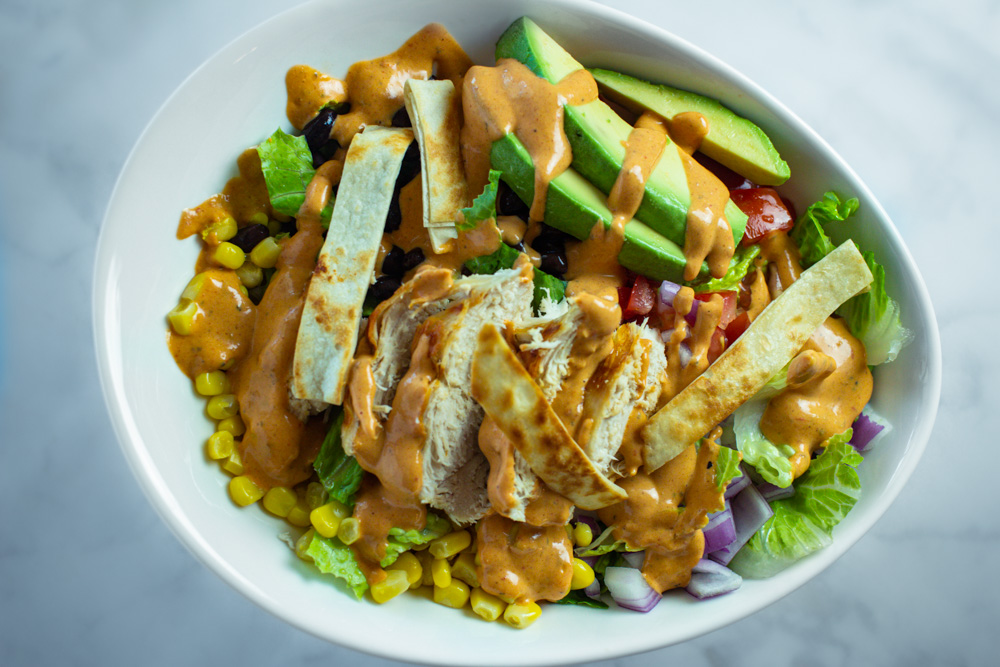 Prepared southwest salad topped with corn, black beans, chopped tomatoes, chopped onions, avocado slices, chicken, and crisp tortilla strips.