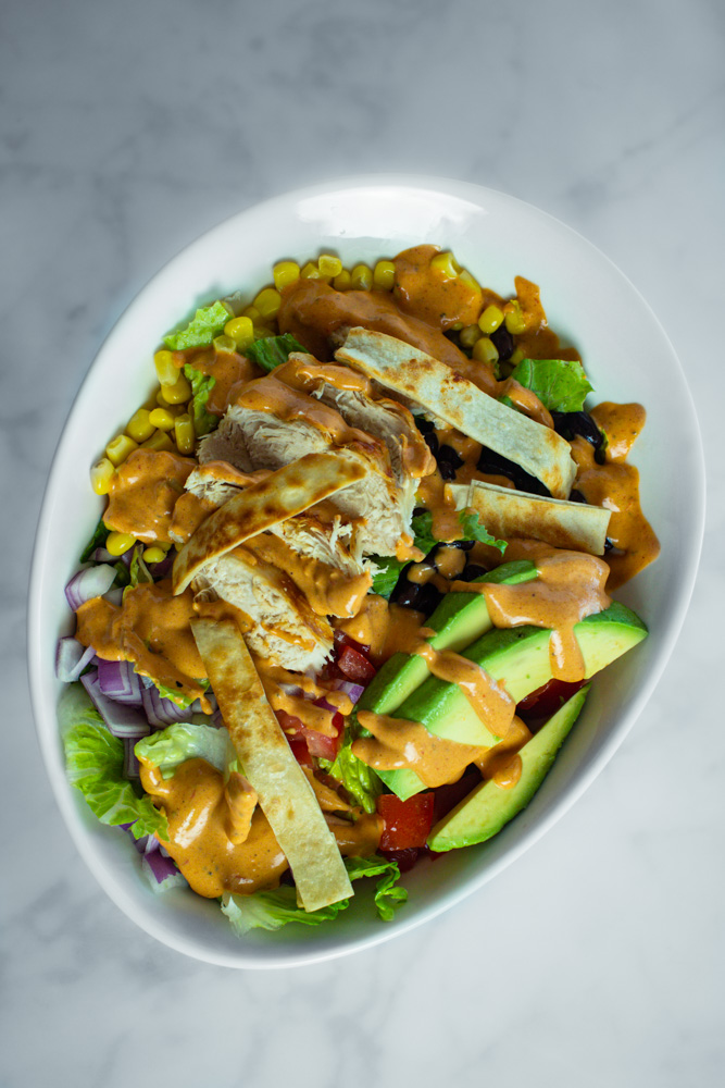 Prepared southwest salad topped with corn, black beans, chopped tomatoes, chopped onions, avocado slices, chicken and crisp tortilla strips.