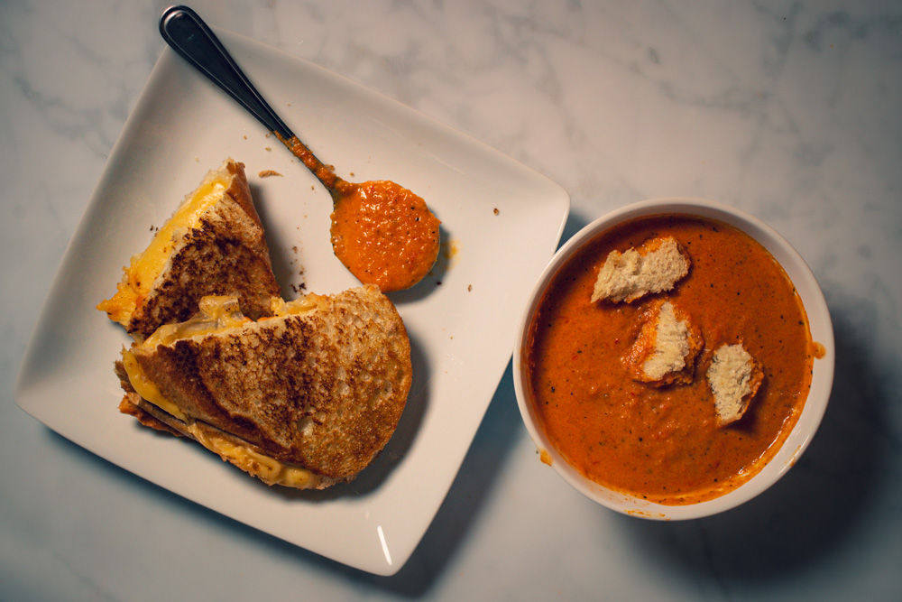 Grilled cheese sandwich cut in half on a plate sitting next to a bowl of creamy tomato basil soup made from fresh tomatoes.