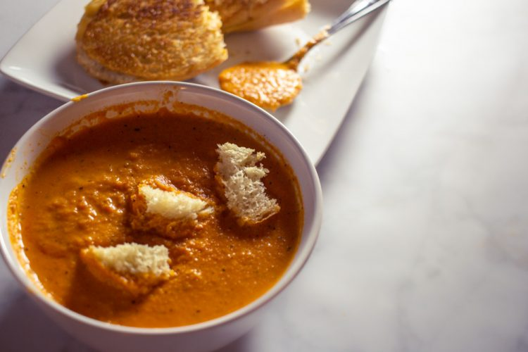 Bowl of tomato soup with croutons and grilled cheese in the background